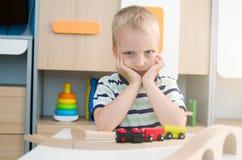 Rapaz pequeno triste furado que senta-se na tabela foto de stock royalty free
