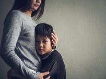 Rapaz pequeno triste que está sendo abraçado por sua mãe em casa fotos de stock