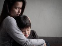 Rapaz pequeno triste que está sendo abraçado por sua mãe em casa imagem de stock royalty free
