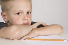 Rapaz pequeno triste que faz seus trabalhos de casa. Foto de Stock Royalty Free
