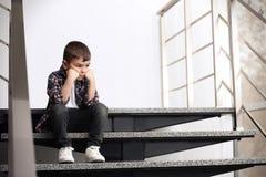 Rapaz pequeno triste que senta-se em escadas fotografia de stock