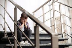 Rapaz pequeno triste que senta-se em escadas fotos de stock royalty free