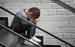 Rapaz pequeno triste que senta-se em escadas fotos de stock