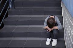 Rapaz pequeno triste que senta-se em escadas fotografia de stock royalty free