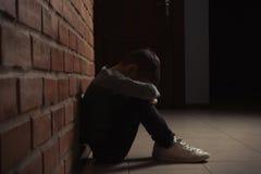 Rapaz pequeno triste que senta-se no assoalho perto da parede de tijolo fotos de stock