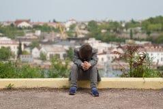 Rapaz pequeno triste que senta-se no freio Fotos de Stock