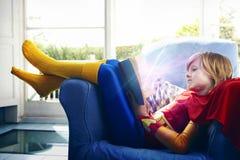 Rapaz pequeno vestido como um super-herói que lê um livro Fotos de Stock Royalty Free