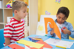 Rapazes pequenos bonitos que cortam as formas de papel na sala de aula Fotos de Stock Royalty Free