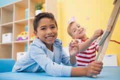 Rapazes pequenos bonitos que fazem a arte na sala de aula Imagem de Stock