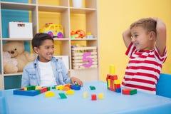 Rapazes pequenos bonitos que jogam com blocos de apartamentos Imagens de Stock