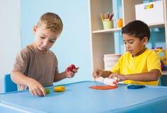 Rapazes pequenos bonitos que jogam com modelagem da argila na sala de aula Fotografia de Stock Royalty Free