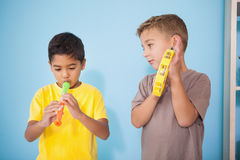 Rapazes pequenos bonitos que jogam instrumentos musicais na sala de aula Fotografia de Stock Royalty Free