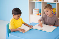 Rapazes pequenos bonitos que leem na mesa na sala de aula Fotos de Stock
