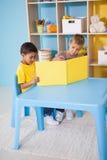 Rapazes pequenos bonitos que leem na mesa na sala de aula Fotografia de Stock Royalty Free