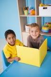 Rapazes pequenos bonitos que leem na mesa na sala de aula Imagem de Stock