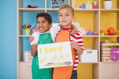 Rapazes pequenos bonitos que mostram a pintura do dia de pais Fotos de Stock Royalty Free