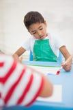 Rapazes pequenos bonitos que pintam na tabela na sala de aula Foto de Stock Royalty Free