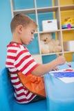 Rapazes pequenos bonitos que pintam na tabela na sala de aula Foto de Stock