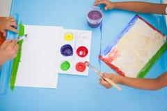 Rapazes pequenos bonitos que pintam na tabela na sala de aula Imagem de Stock Royalty Free