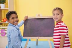 Rapazes pequenos bonitos que tiram no quadro Fotografia de Stock Royalty Free