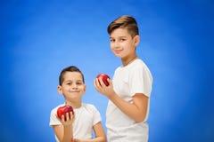 Rapazes pequenos consideráveis com as duas maçãs vermelhas Retrato do estúdio sobre o fundo azul Foto de Stock Royalty Free