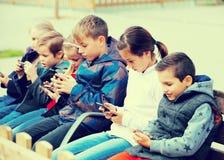 Rapazes pequenos e meninas que sentam-se com tabuletas Imagem de Stock