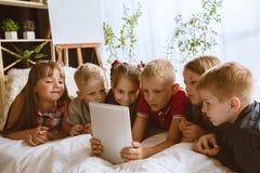 Rapazes pequenos e meninas que usam dispositivos diferentes em casa imagem de stock royalty free