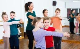 Rapazes pequenos felizes e meninas que dançam a dança dos pares Imagens de Stock