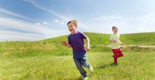 Rapazes pequenos felizes que correm fora Imagem de Stock Royalty Free