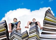 Rapazes pequenos na grande pilha de livros Imagens de Stock Royalty Free