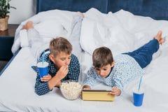 rapazes pequenos que comem a pipoca e que bebem a soda ao descansar imagem de stock