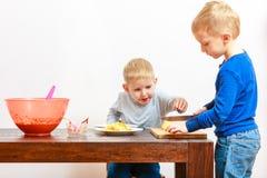 Rapazes pequenos que cortam a maçã com uma faca de cozinha Foto de Stock Royalty Free