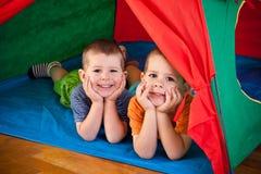Rapazes pequenos que encontram-se dentro da barraca colorida Foto de Stock Royalty Free