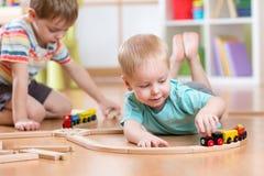 Rapazes pequenos que jogam com grupo de madeira do trem Fotografia de Stock Royalty Free
