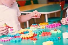 Rapazes pequenos que jogam com os tijolos plásticos coloridos na tabela Crianças que têm o divertimento e que constroem fora do c Fotos de Stock Royalty Free