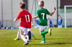 Rapazes pequenos que jogam o jogo de futebol do futebol no campo de esportes Fotografia de Stock