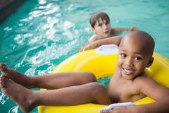 Rapazes pequenos que nadam com anel de borracha Fotografia de Stock