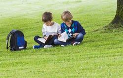 Rapazes pequenos que sentam-se na grama em um parque e em livros de leitura Escola, educação, conceito dos povos Fotografia de Stock Royalty Free