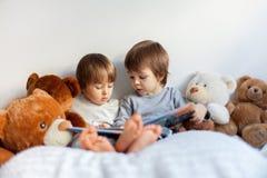 Rapazes pequenos, sentando-se na cama, lendo um livro fotos de stock royalty free