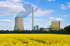Field and coal plant. Field and power plant under a blue sky stock photography