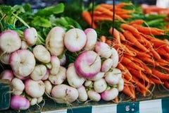 Rapen en wortelen op landbouwersmarkt in Parijs, Frankrijk Stock Afbeelding