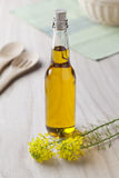 Rapeseed oil in a bottle. With yellow flowers Stock Photography