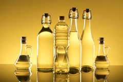 Rapeseed oil concept. Vegetable oil made from rapeseed in bottles on glass table Stock Image