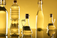 Rapeseed oil concept. Vegetable oil made from rapeseed in bottles on glass table Royalty Free Stock Photos