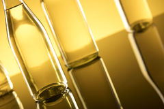 Rapeseed oil concept. Vegetable oil made from rapeseed in bottles on glass table Stock Photography