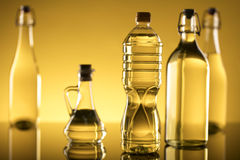 Rapeseed oil concept. Vegetable oil made from rapeseed in bottles on glass table Stock Images