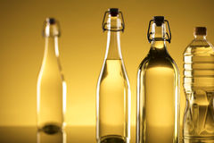 Rapeseed oil concept. Vegetable oil made from rapeseed in bottles on glass table Royalty Free Stock Images