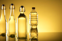 Rapeseed oil concept. Vegetable oil made from rapeseed in bottles on glass table Royalty Free Stock Image