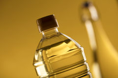Rapeseed oil concept. Vegetable oil made from rapeseed in bottles on glass table Stock Photo
