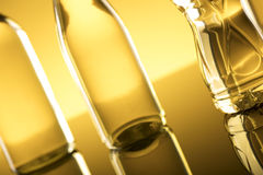 Rapeseed oil concept. Vegetable oil made from rapeseed in bottles on glass table Royalty Free Stock Photography